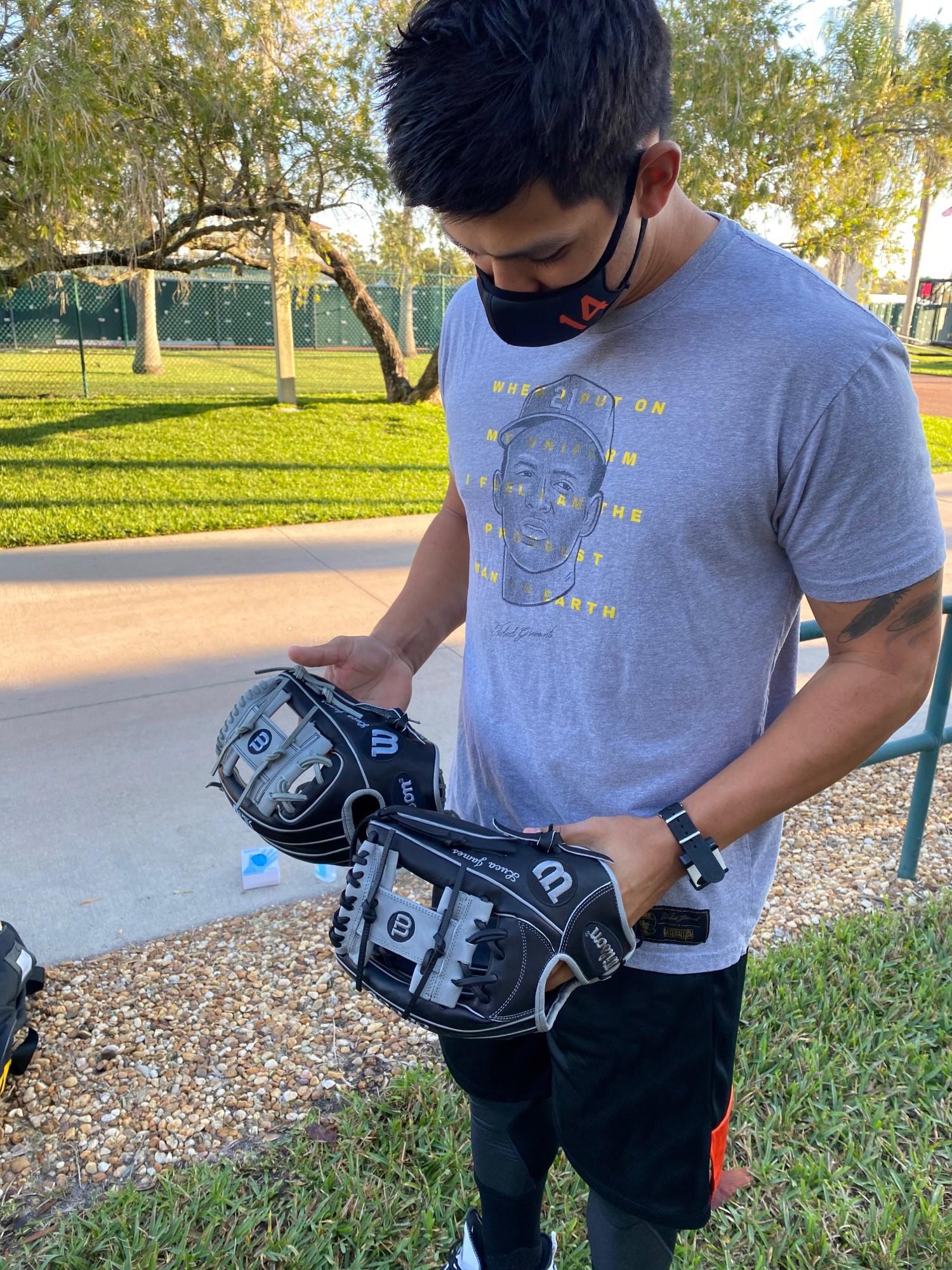 Rio Ruiz holding two wilson ball gloves