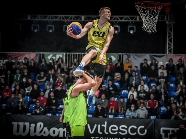 FIBA player leaping towards basket while being guarded